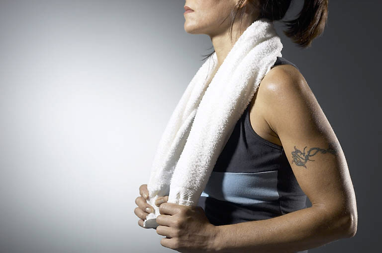 Woman with tattooed arm about to exercise