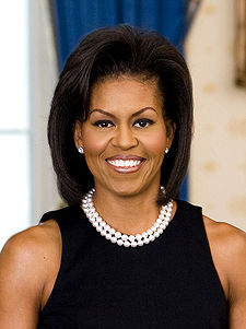 Michelle Obama wearing a black dress and pearls